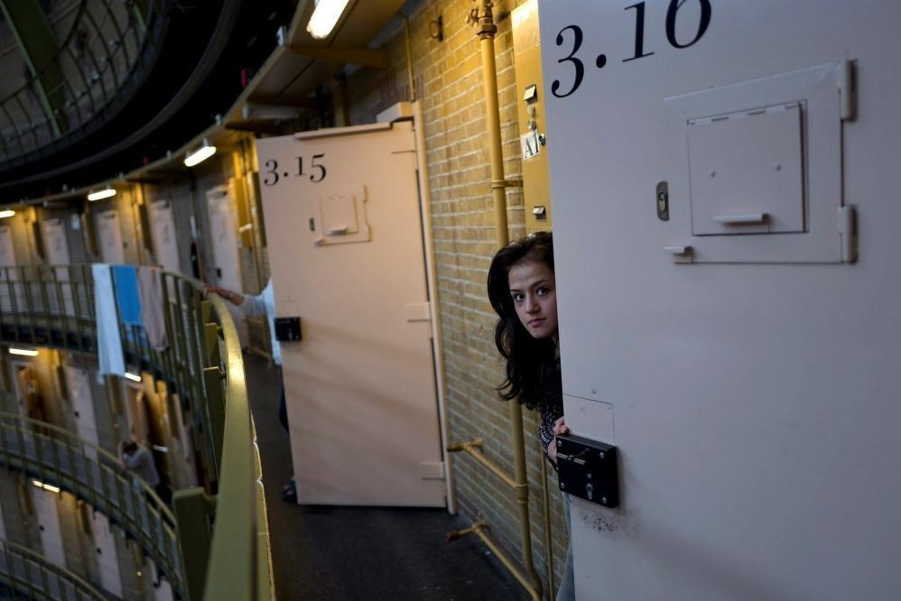 An Afghan refugee peeks through the door of her room at the former prison of De Koepel in Haarlem, Netherlands.