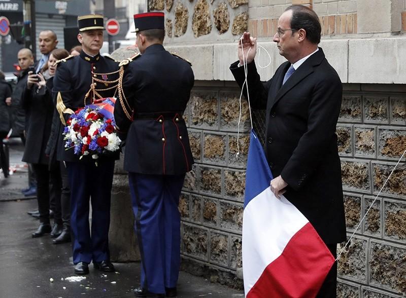 French President Francois Hollande unveils a commemorative plaque next to the ,La Belle Equipe, bar and restaurant, in Paris, France, Sunday, Nov. 13, 2016. (AP Photo)