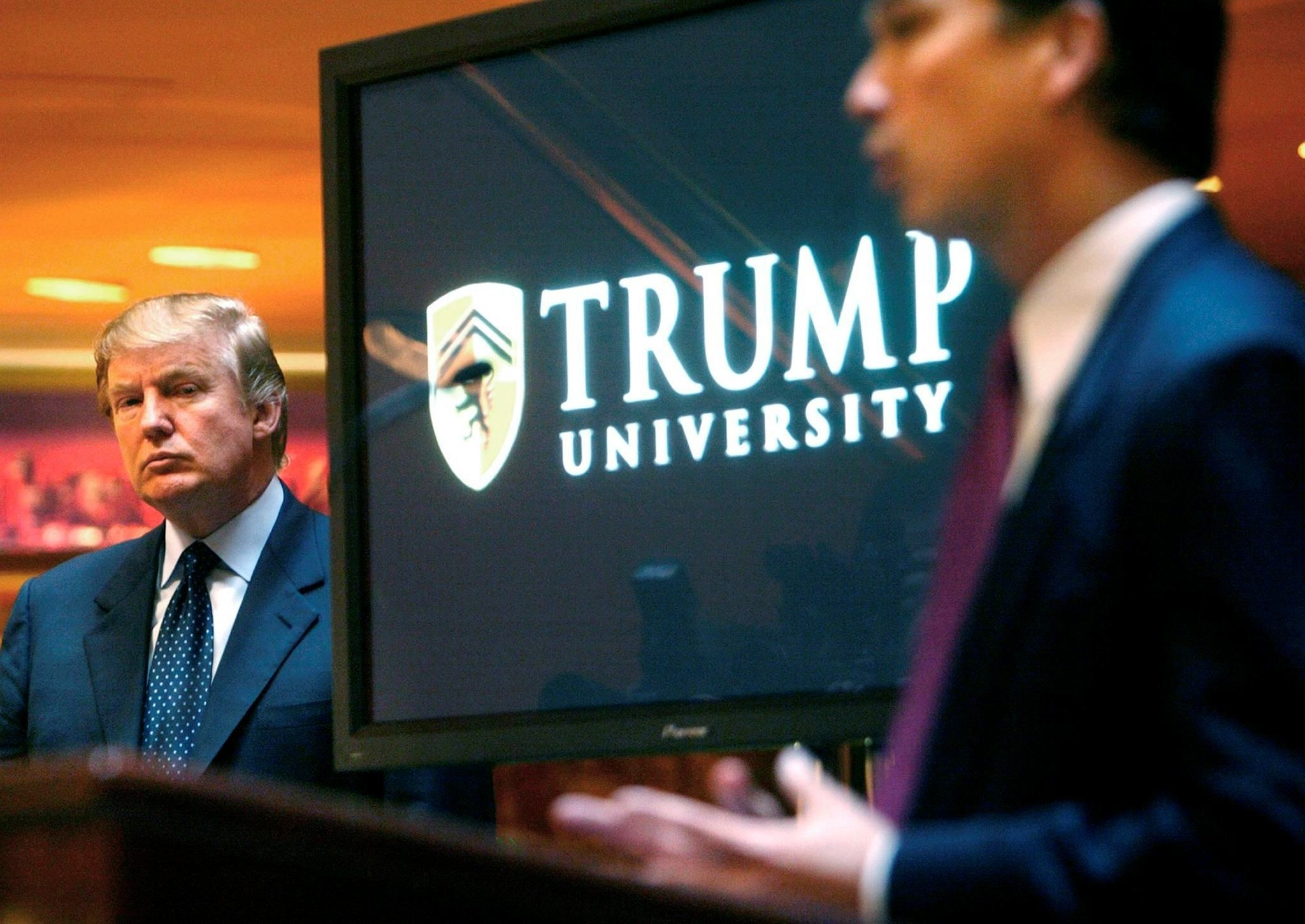 Donald Trump, left, listens as Michael Sexton introduces him at a news conference in New York where he announced the establishment of Trump University. (AP Photo)