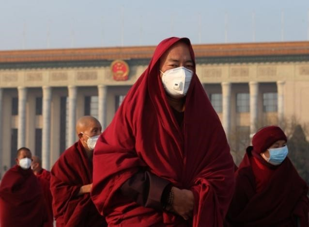 Monks wearing masks walk at Tiananmen Square during a polluted day in Beijing.
