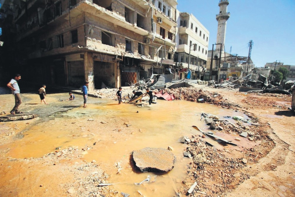 Children play with water from a burst water pipe at a site hit by an airstrike in Aleppo's opposition-controlled al-Mashad neighborhood, Syria, Sept. 30.