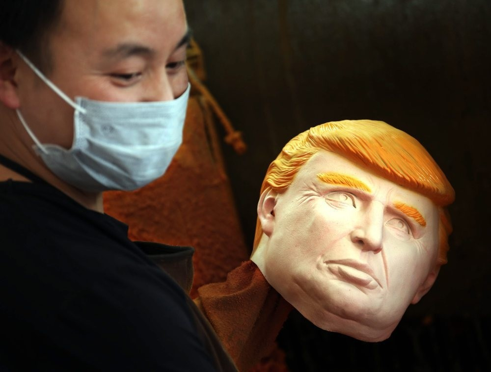 A man works on latex masks of U.S. presidential candidate Donald Trump at a factory in Pujiang county in east China's Zhejiang province. Orders for Donald Trump and Hilary Clinton masks have both exceed 500,000 pieces from the factory.