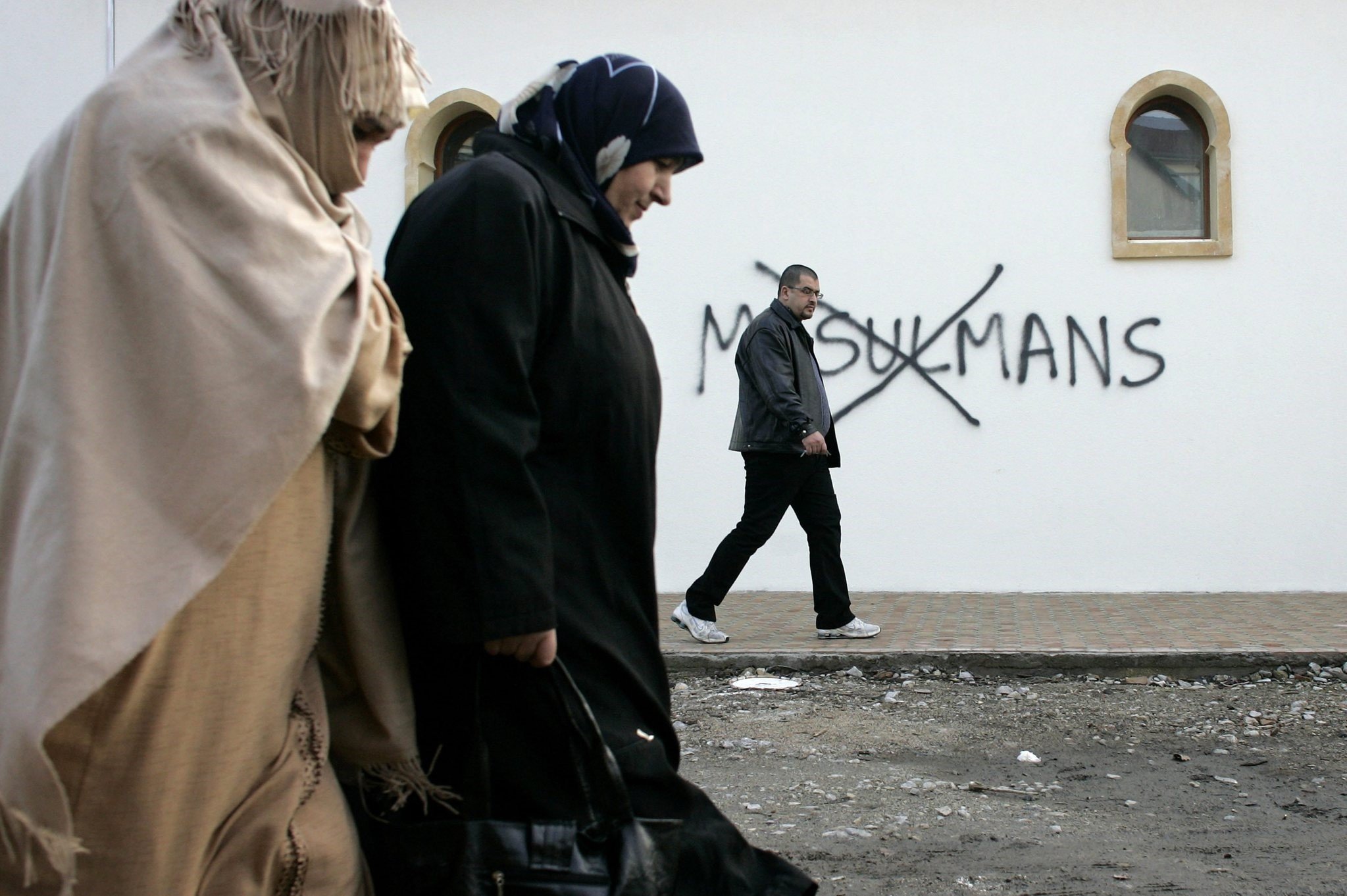 In this Monday Feb. 8, 2010 file photo, Muslim residents walk past racial slurs painted on the walls of a mosque in the town of Saint-Etienne, central France. (AP Photo)
