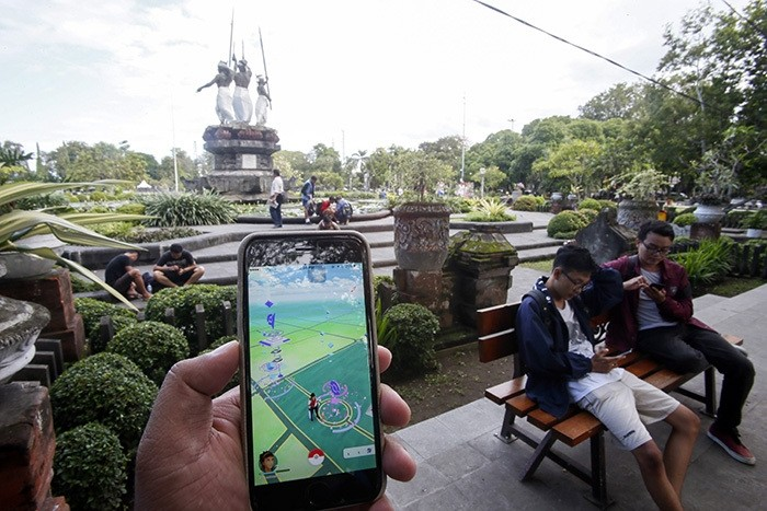 A person plays with Pokemon Go on his mobile phone at a park in Denpasar, Bali, Indonesia, 20 July 2016. (EPA Photo)