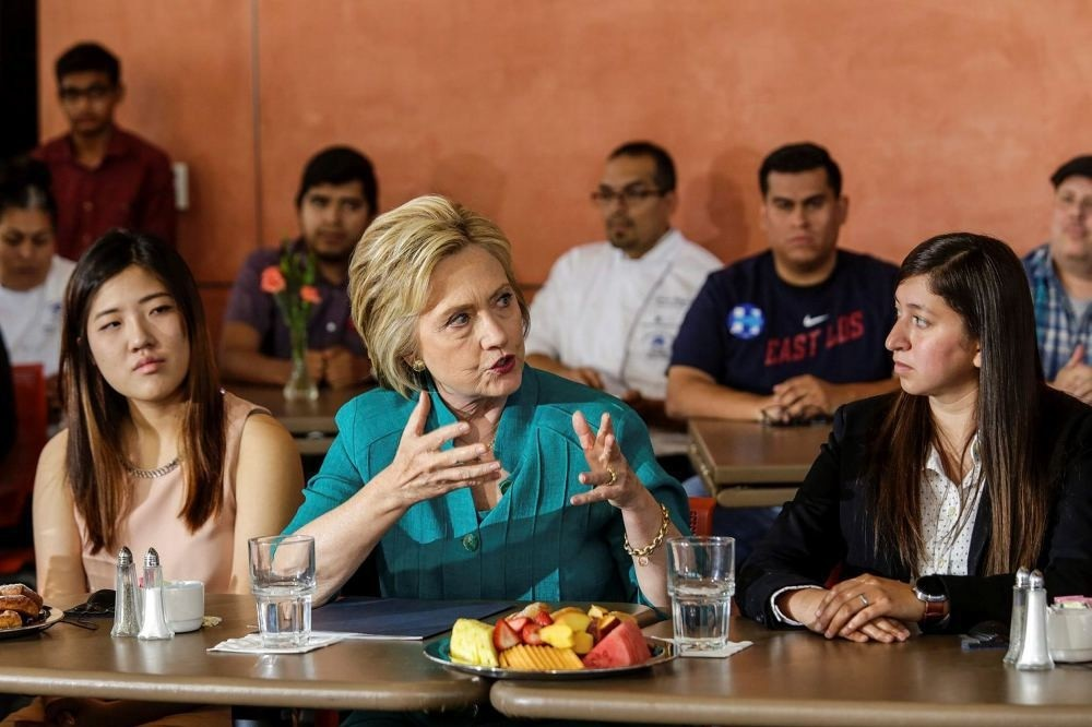 Democratic presidential candidate Hillary Clinton (C) holds a conversation on immigration.