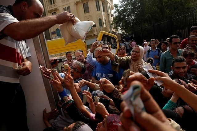 A policeman tries with other Egyptians to buy subsidised sugar from a government truck after a sugar shortage in retail stores across the country in Cairo, Egypt. (Reuters Photo)