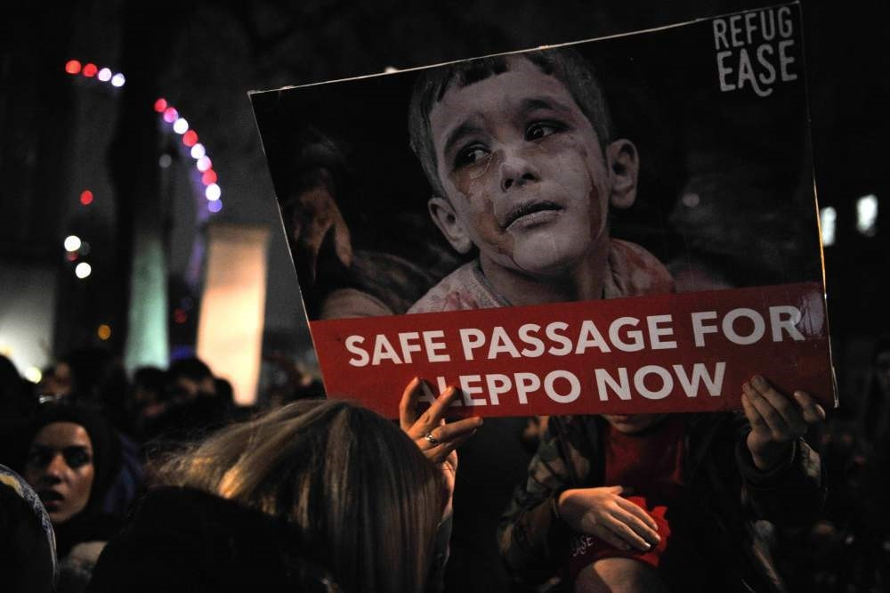 Protesters hold placards during a demonstration in solidarity with the inhabitants of the embattled Syrian city of Aleppo, outside the entrance to Downing Street, in central London on December 13, 2016.