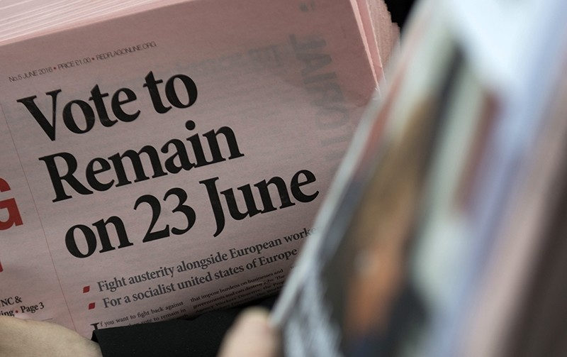 A participant holds a newspaper showing 'Vote to Remain on 23 June' headline as members of the public take part in a 'Remain In' Rally in Trafalgar Square, Central London, Britain (EPA Photo)