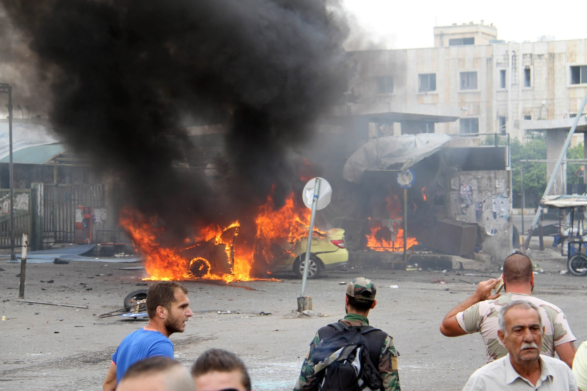 A Syrian army soldier and civilians inspect the damage after explosions hit the Syrian city of Tartous, in this handout picture provided by SANA on May 23, 2016.