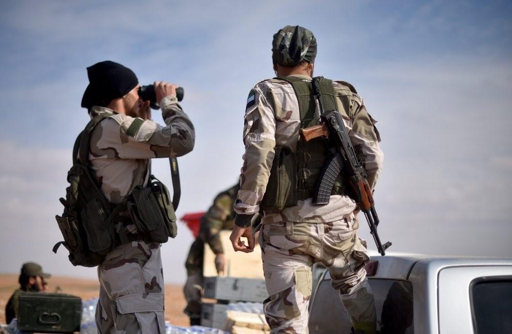 FSA fighters look through binoculars at Daesh targets in Qabasin village, near al Bab on Nov 19.