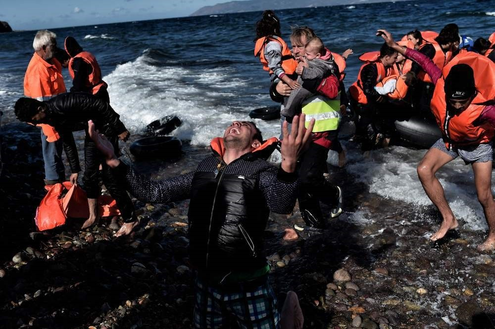 A refugee reacting as he arrives, with other refugees and migrants, on the Greek island of Lesbos after crossing the Aegean Sea from Turkey. (AP Photo)