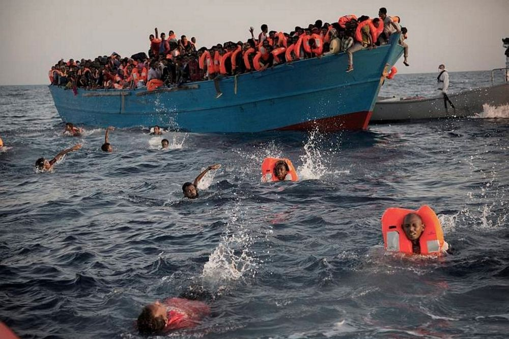 Migrants, most of them from Eritrea, jump into the water from a crowded wooden boat as they are helped by members of an NGO during a rescue operation at the Mediterranean sea, about 13 miles north of Sabratha, Libya, Aug. 29.
