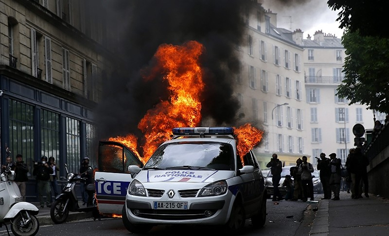 rotesters set a police car on fire during clashes as part as a demonstration, that had been banned, against police violence in the context of ongoing protests over the French government's labor law reform (EPA Photo)