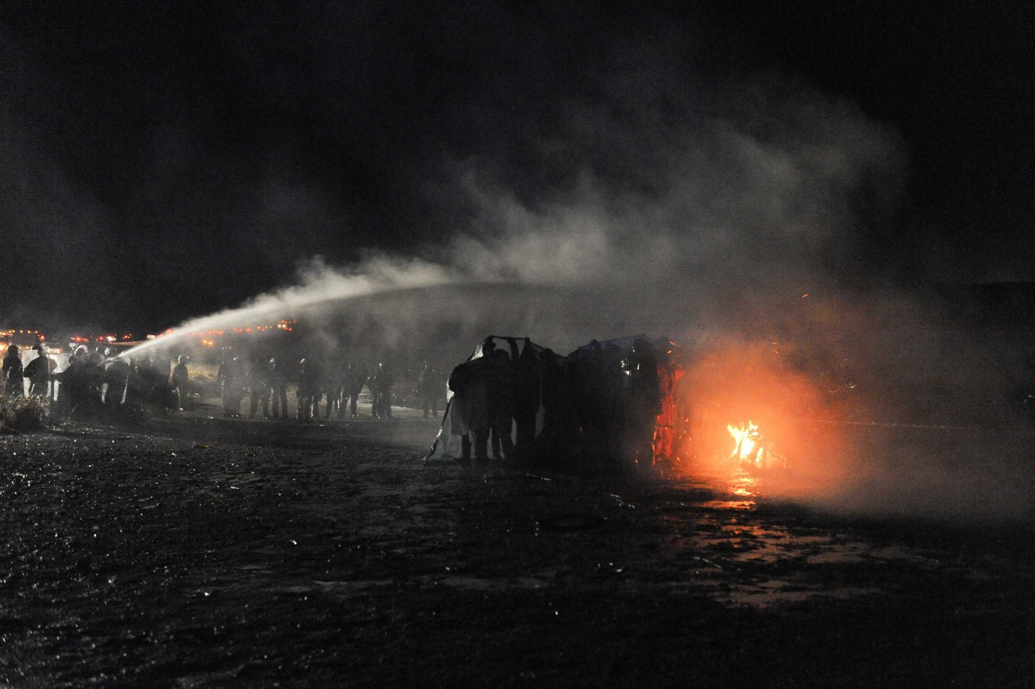 Police use a water cannon to put out a fire started by protesters during a protest against plans to pass the Dakota Access pipeline near the Standing Rock Indian Reservation. (REUTERS Photo)