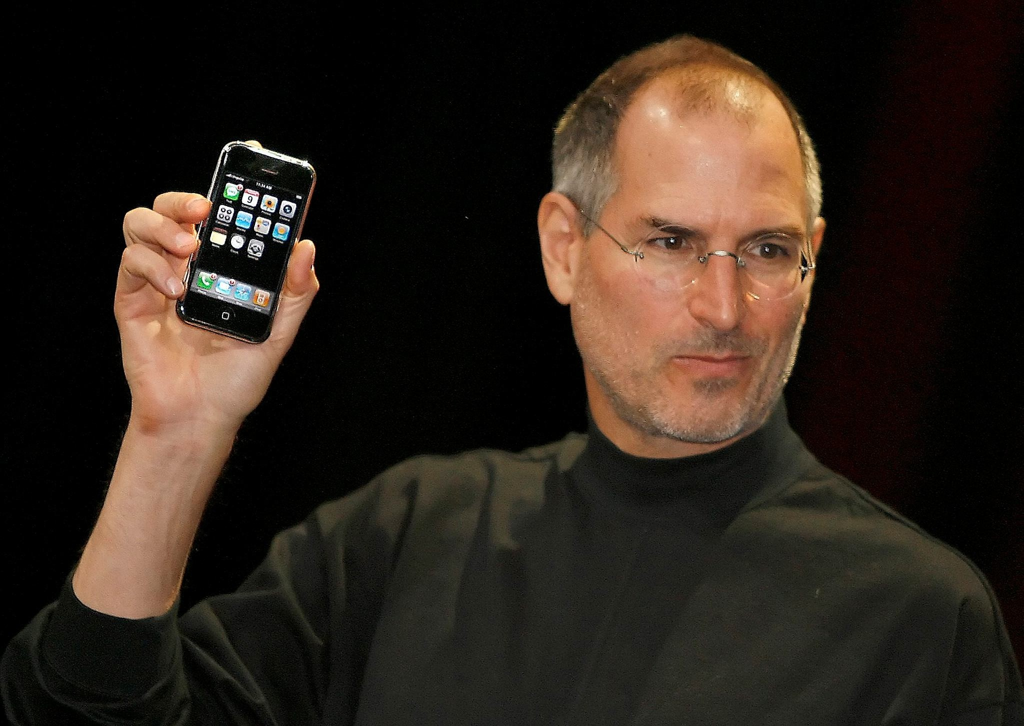 Late Apple founder Steve Jobs holds the very first iPhone (AFP Photo)