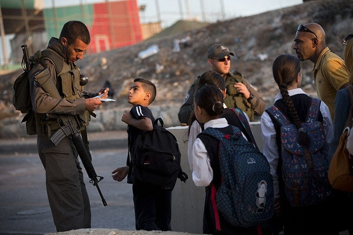 Israeli border police check Palestinian's identification cards at a checkpoint as they exit the Arab neighborhood of Issawiyeh in Jerusalem, Thursday, Oct. 22, 2015. (AP Photo)