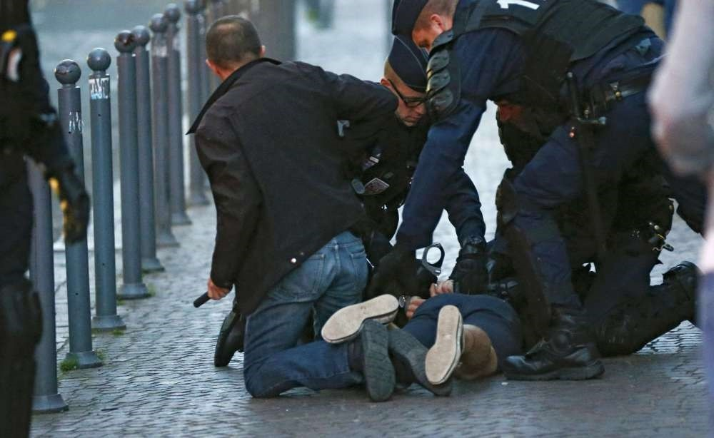 Police detain one of a small group of fans who were fighting in Lille.