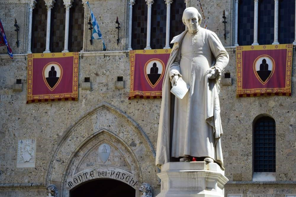 The statue of priest Sallustio Bandini at Piazza Salimbeni stands at the headquarters of the Monte dei Paschi di Siena bank in Tuscany.