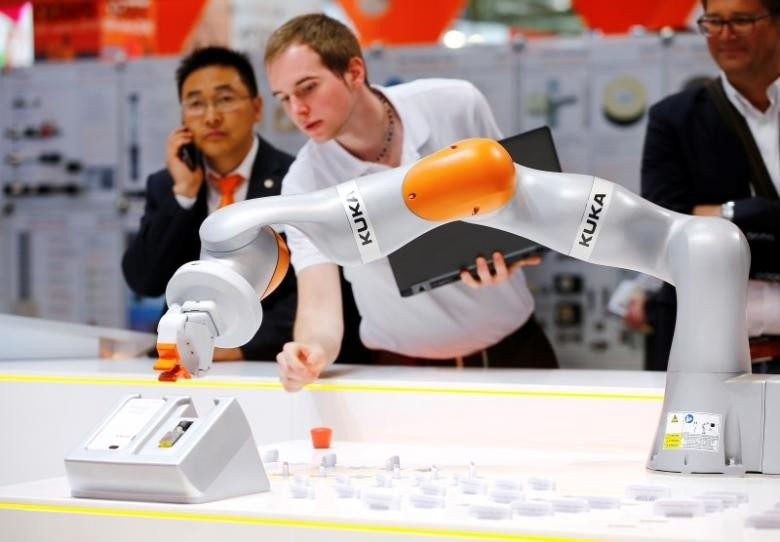 A technician programs a robot arm of German industrial robot maker Kuka at the companyu2019s stand during the Hannover Fair in Hanover.