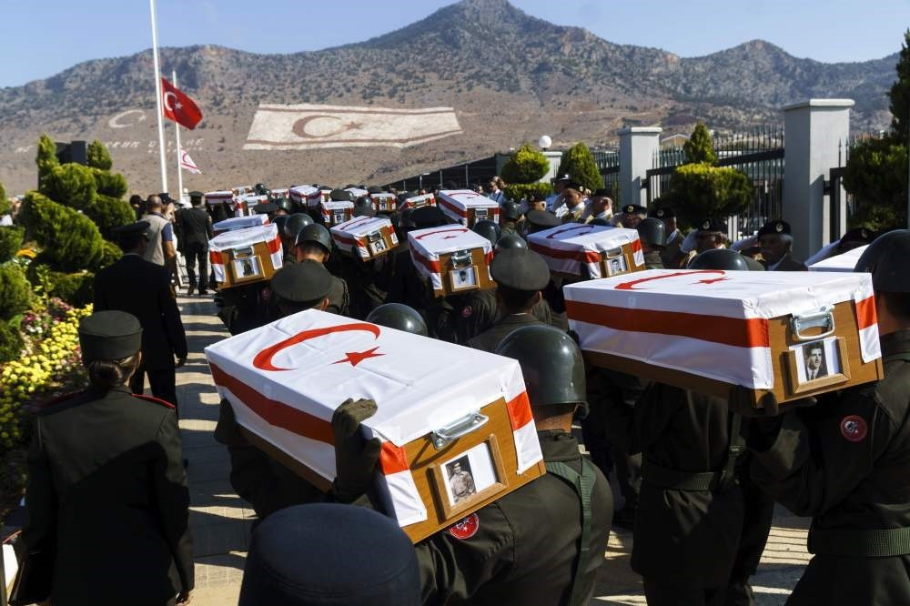 Soldiers carry coffins with remains of 33 villagers.