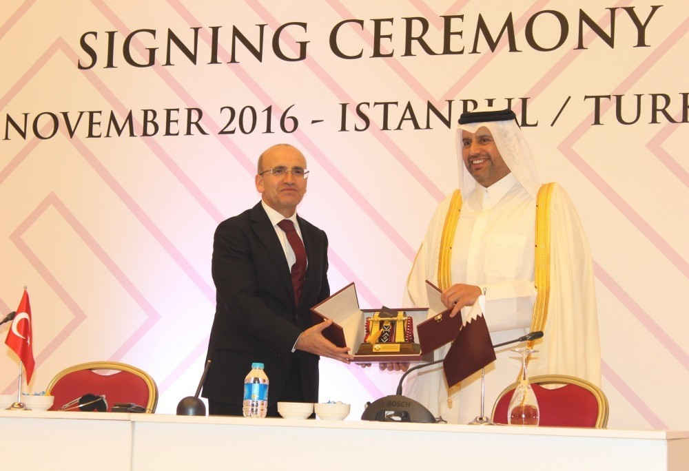 Qatari Minister of Economy Ahmed bin Jassim Al Thani (R) presents a gift to Turkish Deputy Prime Minister Mehmet u015eimu015fek after a signing ceremony between the two countries in Istanbul yesterday.