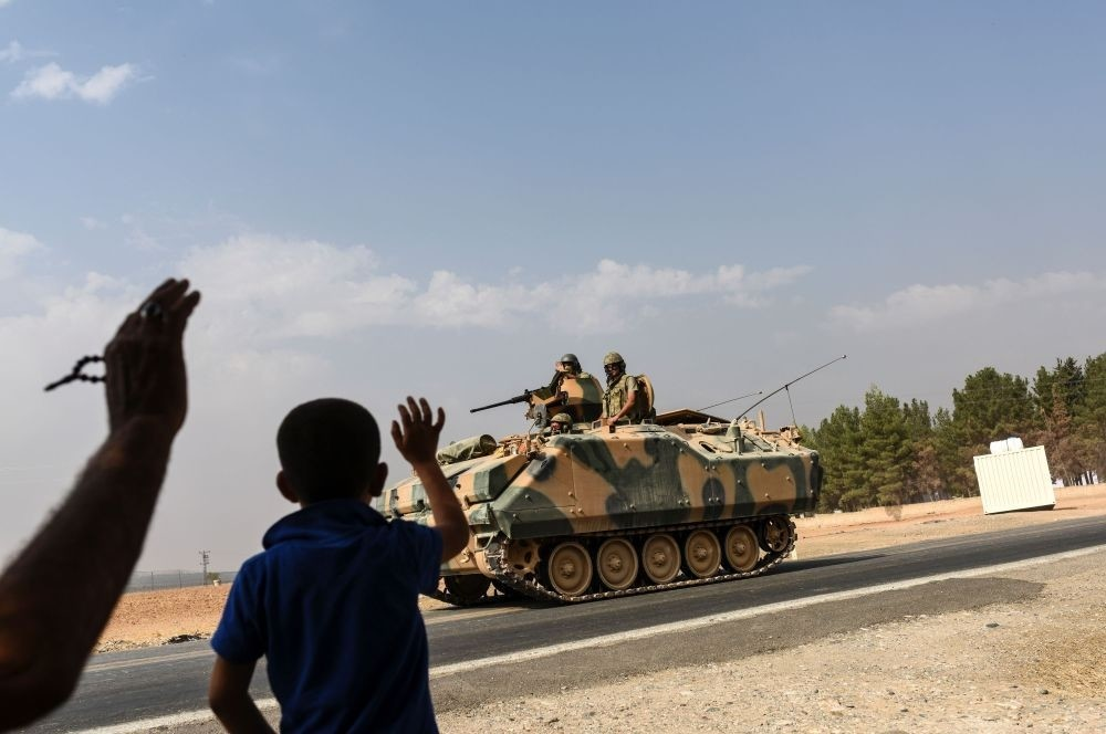 A boy waving to Turkish tank convoy driving into Syria from the Karkamu0131u015f distrcit in Turkey's southern province of Gaziantep on the border wtih Syria, on Aug. 26.