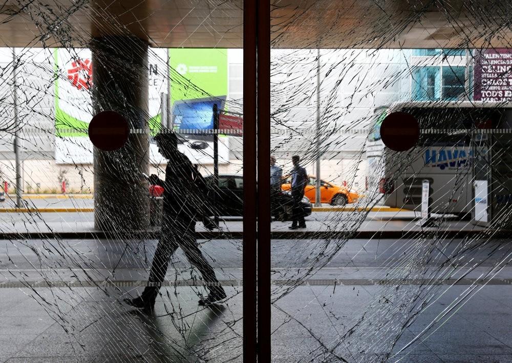A man walks behind shattered glass at Istanbul's Atatu00fcrk International Airport, following Tuesday's blast, June 29.