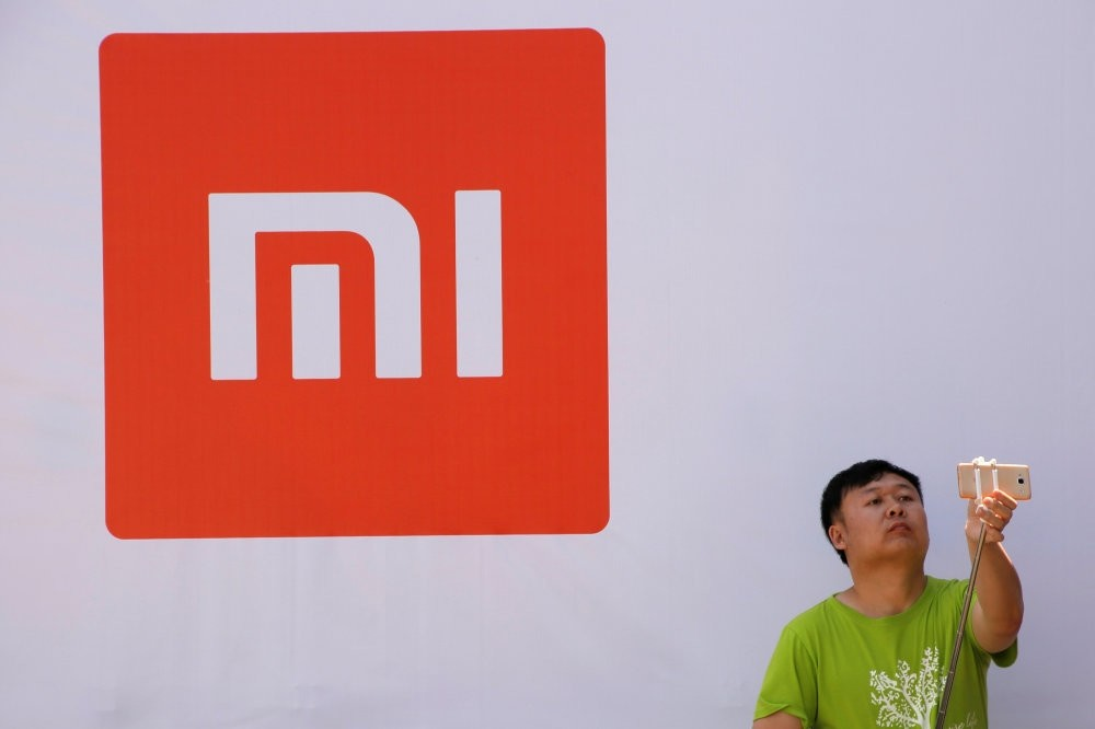 A man takes a selfie in front of the Xiaomi logo.