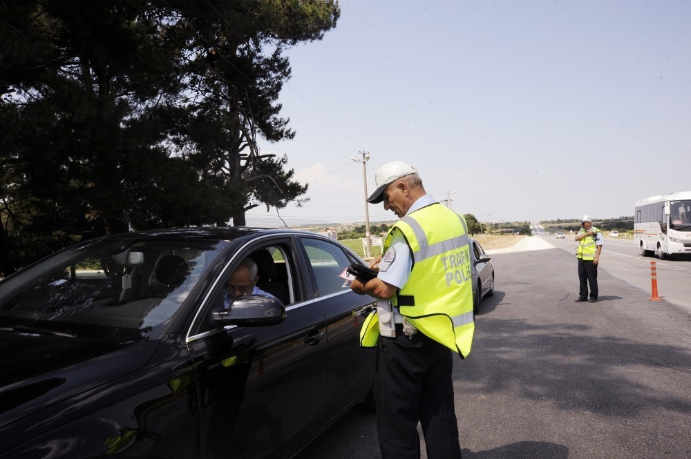 An officer checks the papers of a driver on a road in u00c7anakkale. The route is popular among holidaymakers from big cities in the west and often sees serious accidents.