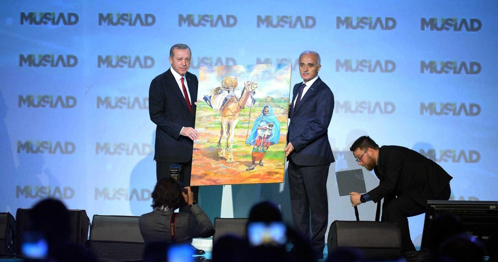 Mu00dcSu0130AD Chairman Nail Olpak (R) presents an African artistu2019s painting to President Erdou011fan.