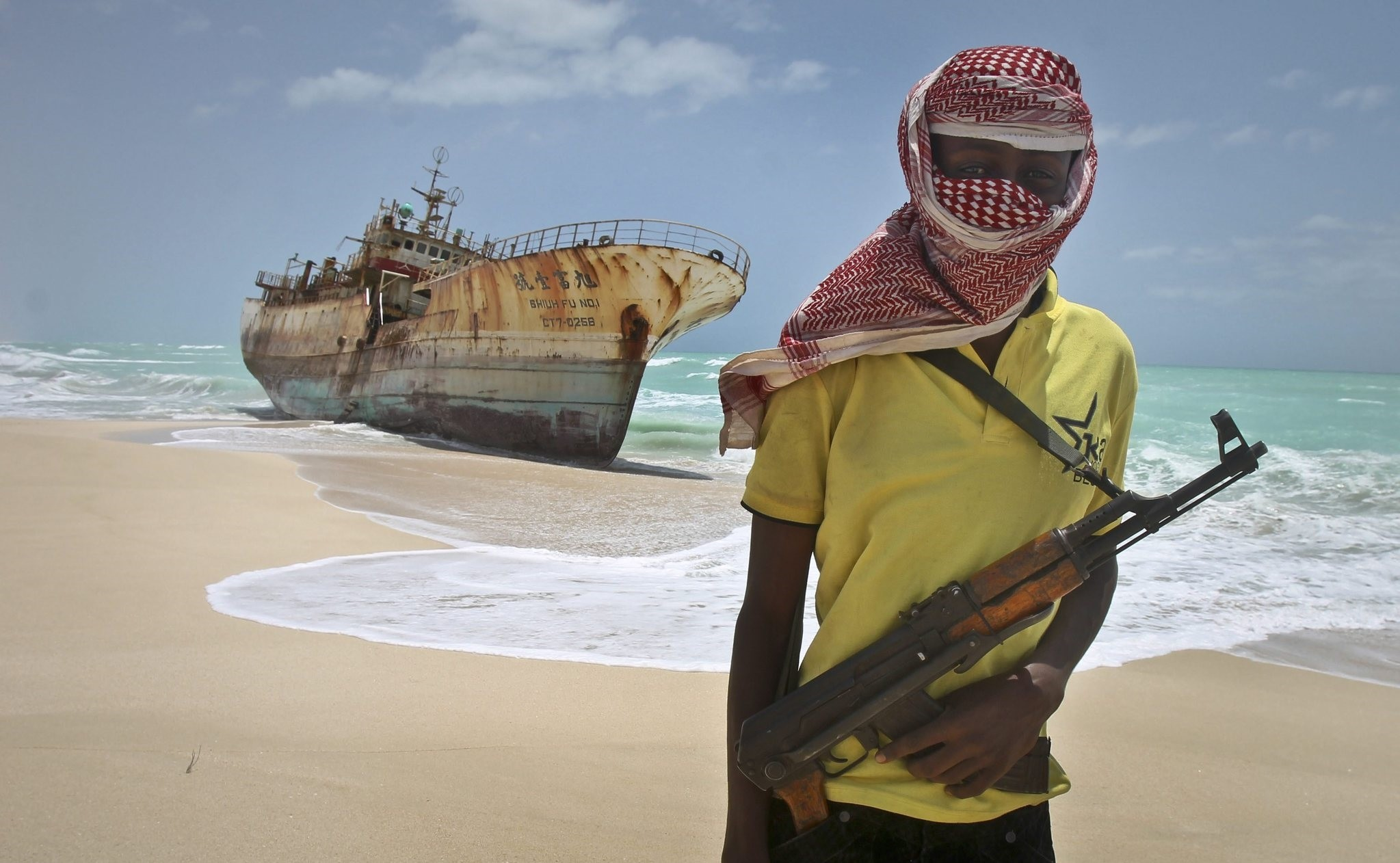 In this Sunday, Sept. 23, 2012 file photo, masked Somali pirate Hassan stands near a Taiwanese fishing vessel that washed up on shore after the pirates were paid a ransom and released the crew. (AP Photo)