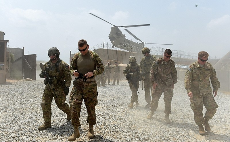 In this photograph taken on August 13, 2015, US army soldiers walk as a NATO helicopter flies overhead at coalition force Forward Operating Base (AFP Photo)
