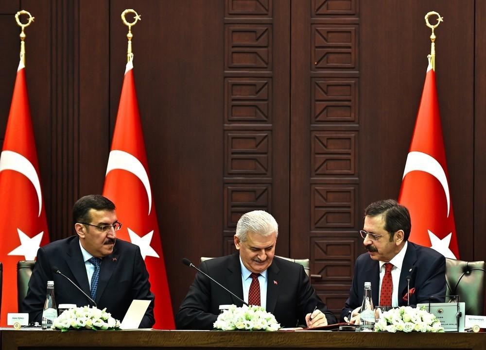 Prime Minister Binali Yu0131ldu0131ru0131m, accompanied by TOBB President Rifat Hisarcu0131klu0131ou011flu on the left and Customs and Trade Minister Bu00fclent Tu00fcfenku00e7i on the right, speaks in Ankara at the launch of the SME loan project.