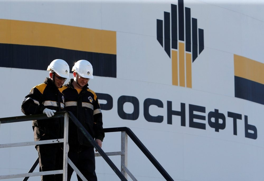 Workers stand next to a logo of Russian Rosneft Oil Company at the central processing facility