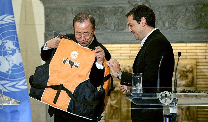 Greek Prime Minister Alexis Tsipras (R) gives United Nations (UN) Secretary General Ban Ki-moon a life vest to try on during their meetin at Maximos Mansion in Athens, Greece, 18 June 2016 (EPA Photo)