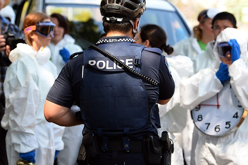 A police officer stands guard as protestors carry clocks to show timing is running out during an Ebola protest event in Brisbane on November15, 2014 (AFP Photo)
