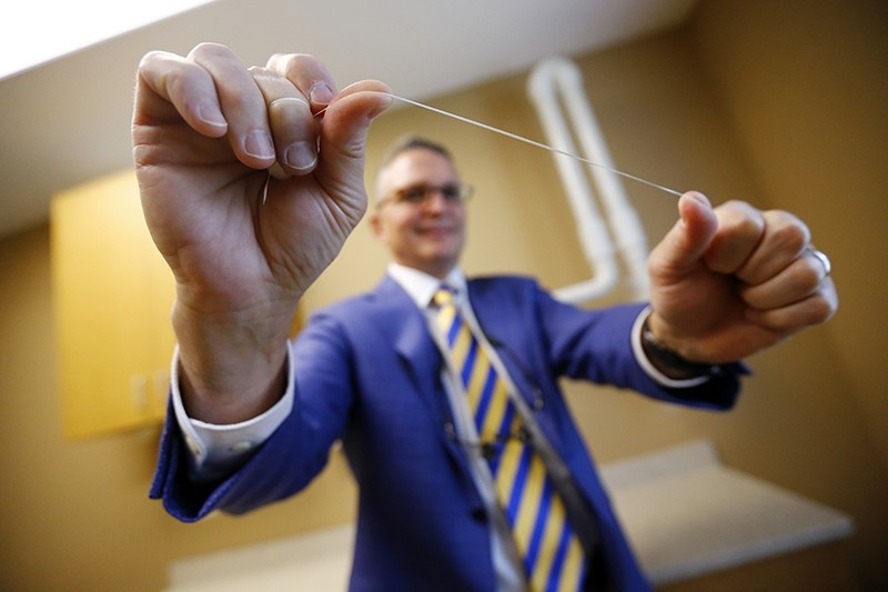 Dr. Wayne Aldredge, president of the American Academy of Periodontology, holds a piece of dental floss at his office in Holmdel, N.J. (AP Photo)