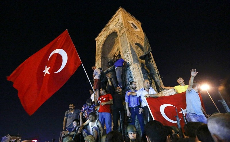 People wave flags as they demonstrate in the Taksim Square in Istanbul, Turkey, July 16, 2016. (Reuters Photo)