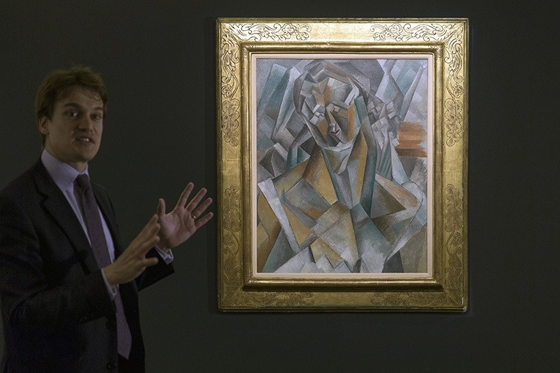 Simon Stock, Sotheby's senior director, senior international specialist, impressionist and modern art, unveils Picasso's 'Femme Assise' during a media preview at Sotheby's in Hong Kong, China, May 27, 2016. (AP Photo)