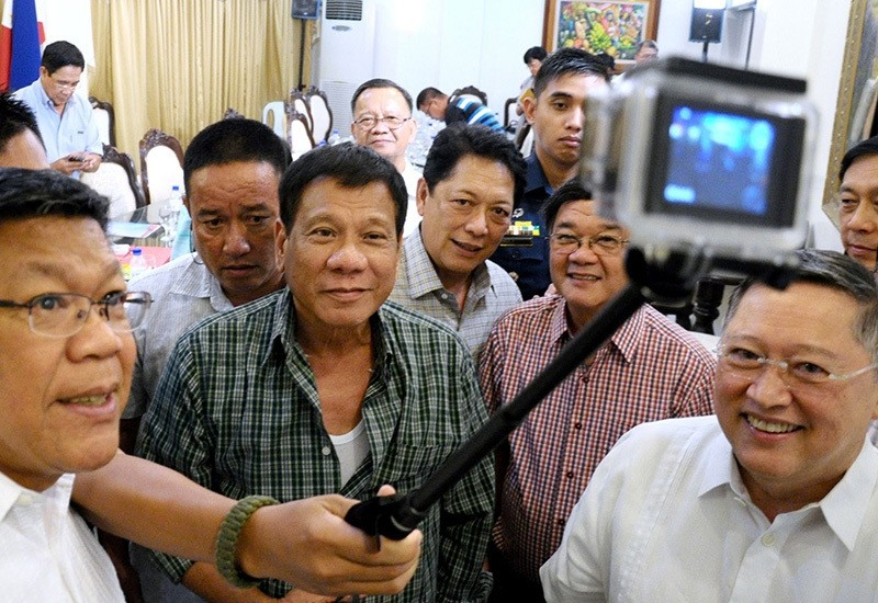Philippines' President-elect Rodrigo Duterte (C) takes a selfie with Cabinet members during a press conference in the southern Philippine city of Davao on May 31, 2016 (AFP)