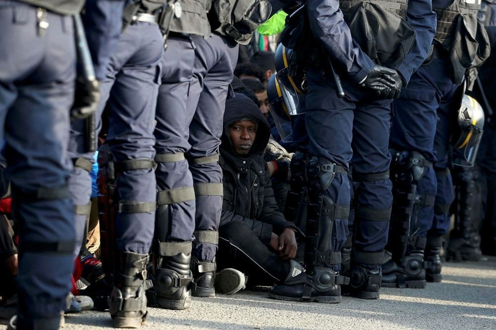 French police stand near as migrants wait in front of a processing center to be registered on the second day of their evacuation during the dismantlement of the camp called the ,Jungle, in Calais, France, Oct. 25.