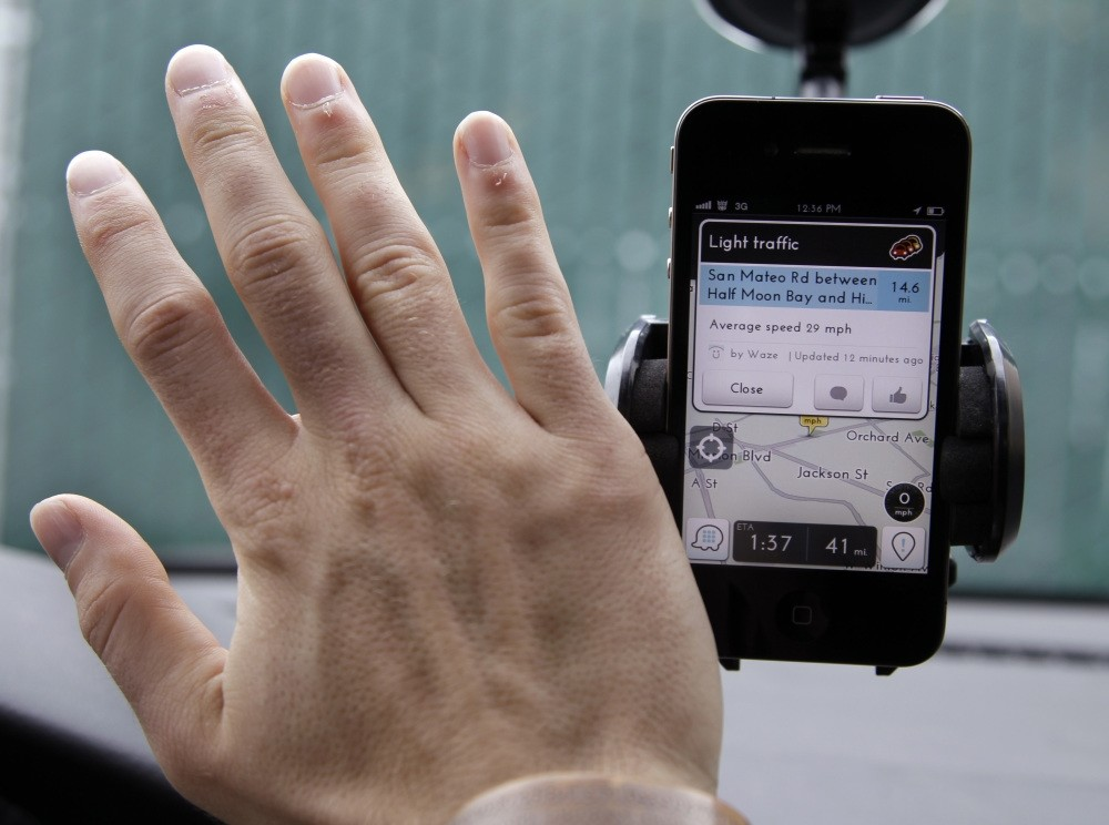 Ben Gleitzman waves his hand over a traffic and navigation app called Waze on his Apple iPhone in a Menlo Park, Calif., parking lot during a demonstration showing traffic conditions on the display.