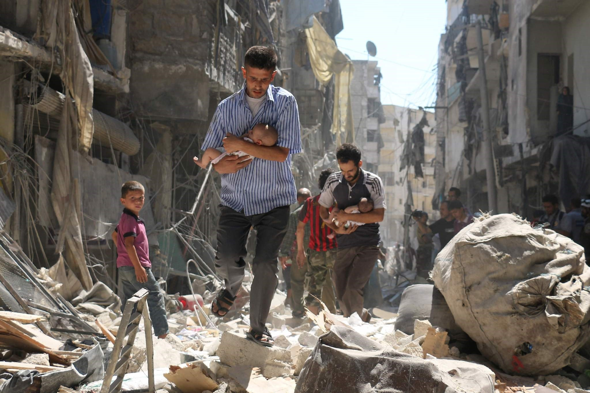 Syrian men carrying babies make their way through the rubble of destroyed buildings following a reported air strike on Aleppo. (AFP Photo)
