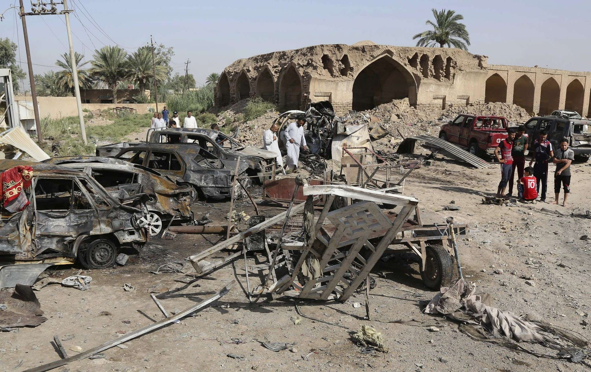 Civilians inspect the scene of a deadly friday night suicide car bombing at a busy market in Khan Beni saad, about 20 miles (30 kilometers) northeast of Baghdad, Iraq, Saturday, July 18, 2015. (AP Photo)