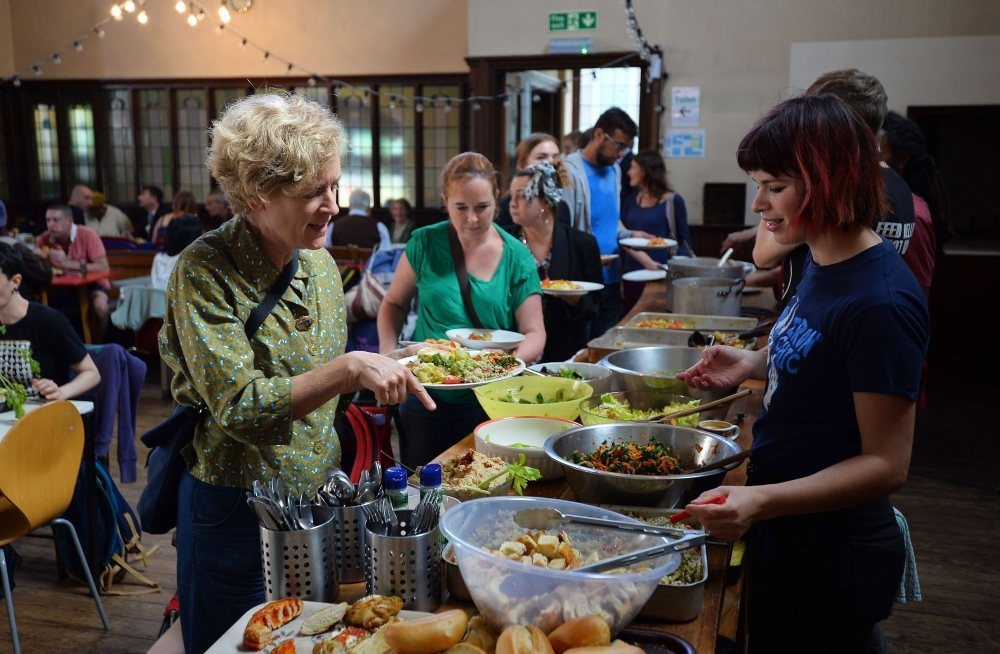 People eat at a Real Junk Food Project cafe in a Church in Brighton, southeast England.