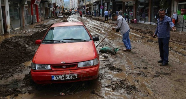 Locals and workers cleared the mud that covered the towns following the floods.