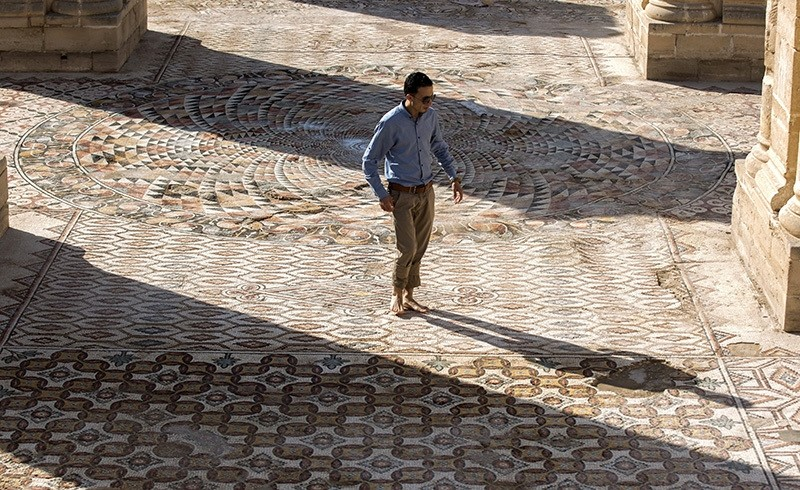 A Palestinian employee of the Palestinian Ministry of Tourism and Antiquities walks on a large Mosaic at Hisham's Palace in the West Bank city of Jericho, 20 October 2016 (EPA Photo)