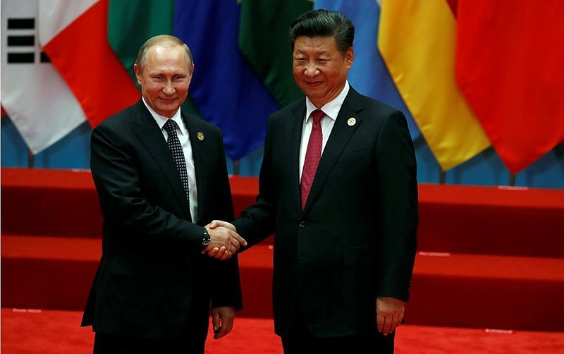 Russian President Vladimir Putin, left, shakes hands with Chinese President Xi Jinping before a group photo session for the G20 Summit (AP Photo)