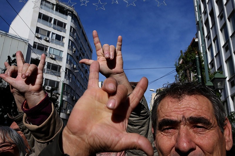 Deaf people make a gesture that in the sign language means 'Victory' as they protest against austerity measures in central Athens, Greece, 02 December 2016. (EPA Photo)