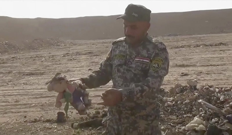 In this Monday, Nov. 7, 2016 frame grab from video, an Iraqi federal police officer holds a stuffed toy at the site of a mass grave in Hamam al-Alil, Iraq. (AP Photo)